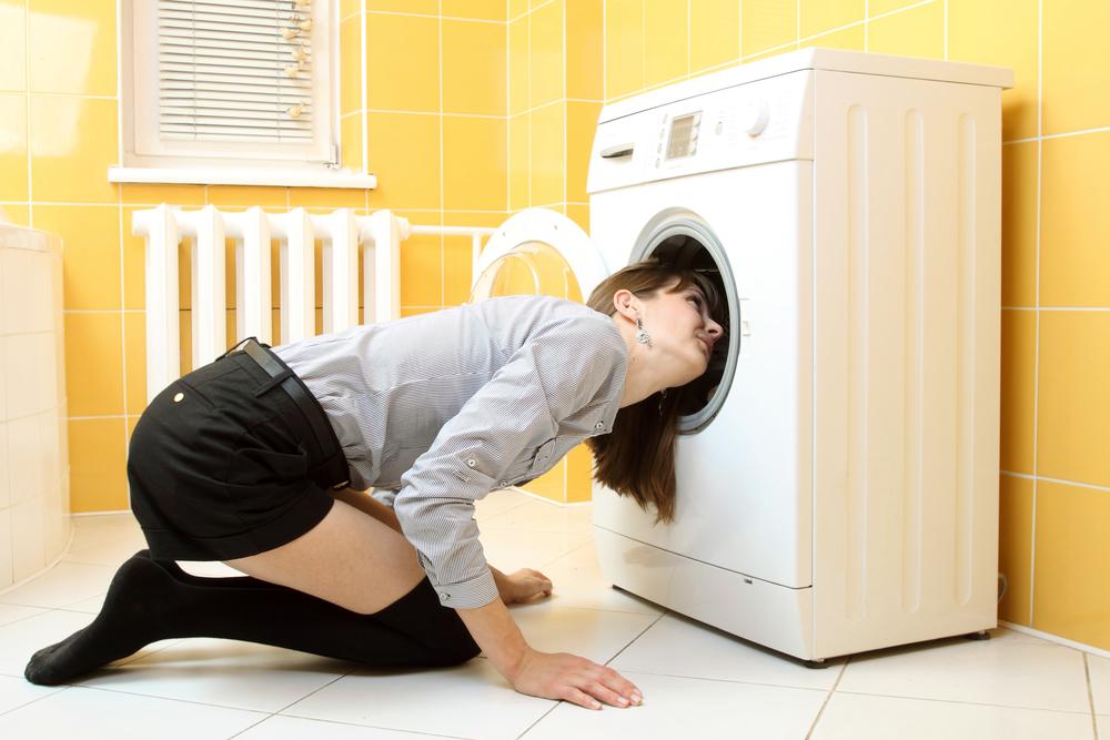 Woman checking a washing machine